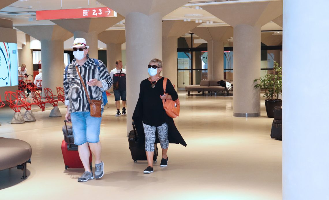 Matkustajapariskunta Katajanokan terminaalin lähtöaulassa maskit kasvoillaan.
